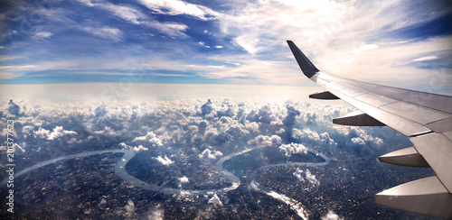 Foto Murales Concepto de viaje en avión .Volando sobre la ciudad hacia el destino. Paisaje al atardecer sobre las nubes.