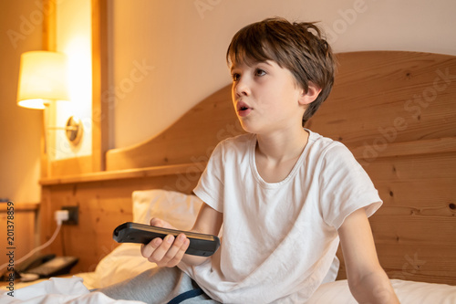 Foto Murales Child on the bed watching TV holding the remote control