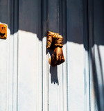 Door with brass knocker in the shape of a hand,  beautiful entrance to the house - 201381620
