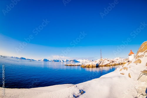 Outdoor view of the shore, all land covered with snow, with blue lake in snowy winter in the Arctic Circle