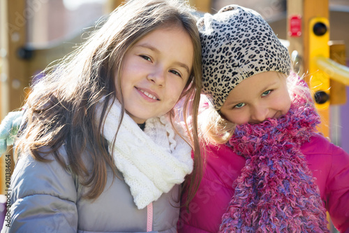 Two girls posing at playground in spring day