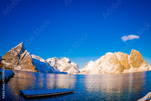 Outdoor view of amazing nature landscape with turquoise water and sunny day in blue sky with a floating structure in the lake and huge mountain covered with snow in Svolvaer