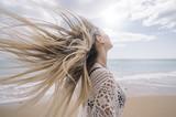 A girl on the beach loosing hair. - 201388089