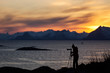Photographer enjoying and taking pictures at beautiful landscape with mountains and colourful clouds at sunset in background. Lofoten Island, Norway.