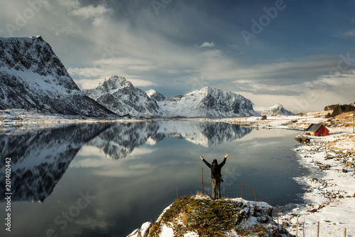 Foto Murales Photographer enjoying and taking pictures at beautiful landscape with mountains and lake reflection in background. Lofoten Island, Norway.