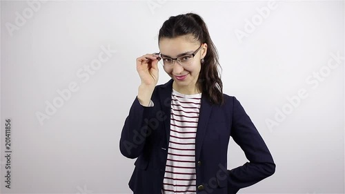 Young beautiful woman in glasses looks at camera and winks