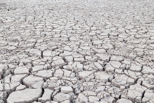 View of cracked and parched gray soil ground after drought
