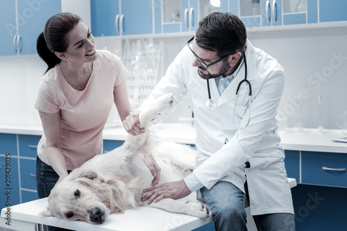 Is he ok. Nice pleasant young woman looking at the doctor and asking about her dog while worrying about him