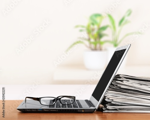 Laptop and black glasses on table