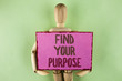 Handwriting text writing Find Your Purpose. Concept meaning life goals Career Searching educate knowing possibilities written on Sticky note paper holding by Wooden Robot Toy on plain background.