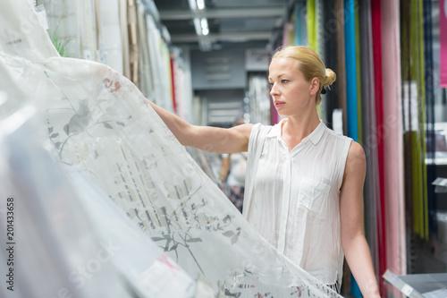 Piękna młoda caucasian kobieta kupuje białe zasłony dla jej mieszkania w nowożytnym domowym wystrojów meblowań sklepie. Zakupy w sklepie detalicznym.
