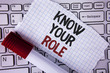 Conceptual hand writing showing Know Your Role. Business photo text define position in work or life Career Life goals active written on Tear Notebook paper placed on the Laptop Marker next to it..