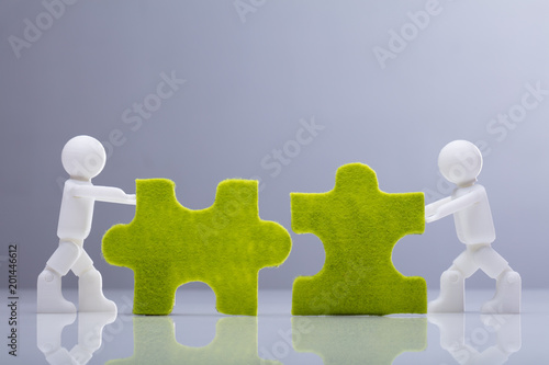 Two Miniature Human Figures Solving Green Jigsaw Puzzles