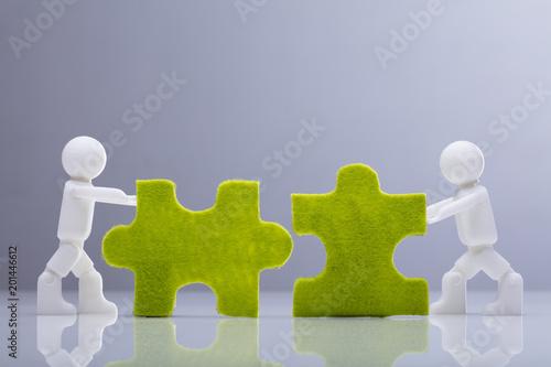 Fridge magnet Two Miniature Human Figures Solving Green Jigsaw Puzzles