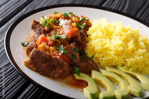 Ekwadorski seco de chivo koźli mięso z garnirunkiem żółty ryż i avocado close-up. poziomy