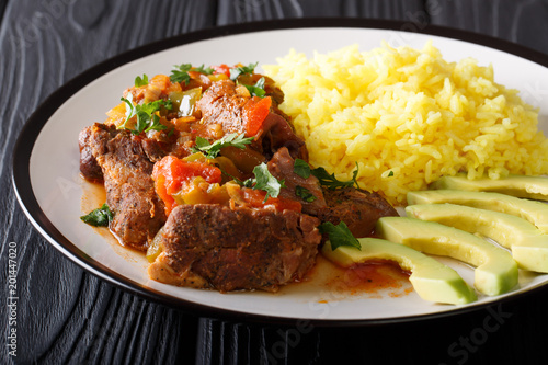 Ecuadorian seco de chive stewed goat meat with a side dish of yellow rice and avocado close-up on a plate. horizontal