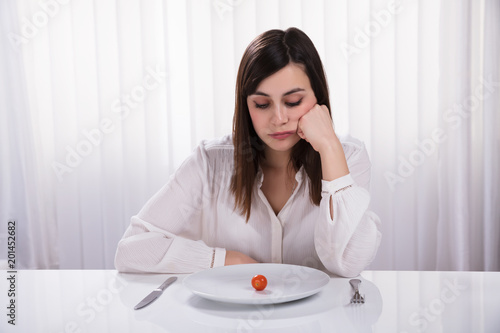 Foto Murales Woman Sitting With Plate Of Cherry Tomato