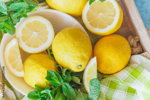 Foto Murales Yellow lemons with mint leaves, wooden background