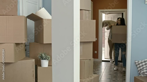 Slowmo of happy Asian woman cardboard box and her cheerful husband carrying carpet walking into new house and chatting