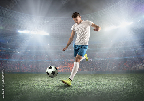 Zobacz obraz Soccer player on a football field in dynamic action at summer da
