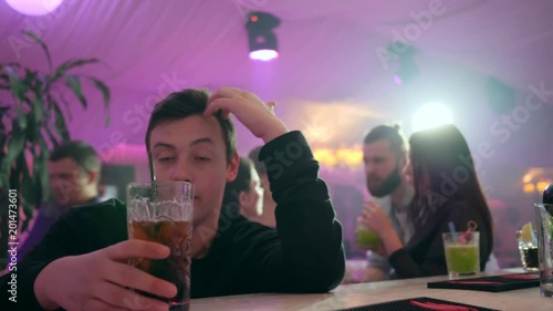 depressed drunk guy drinks chilled alcohol behind the bar stand at nightclub on background of lights