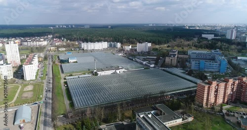 Sticker Panorama from height, view of greenhouses, reflections in glass, city landscape aerial view.