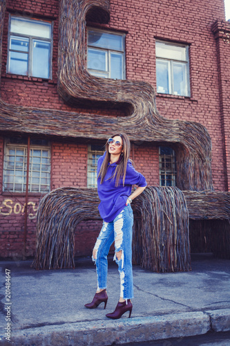 Foto Murales Young fashionable girl standing near a brick wall. Fashion & Style