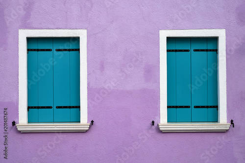 Foto Murales Two windows with bright blue shutters on lilac wall. Italy, Venice, Burano island.
