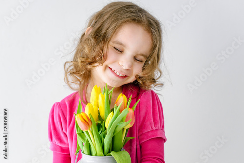 Foto Murales happy baby girl holding a bouquet of yellow tulips. happy mother's Day. international women day.