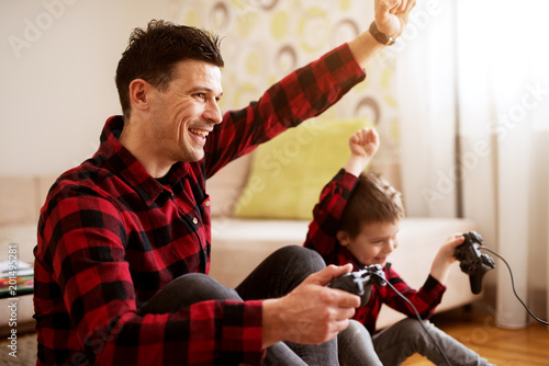 Foto Murales Young cheerful excited father and son in the same red shirt playing console games with gamepads in a bright living room.