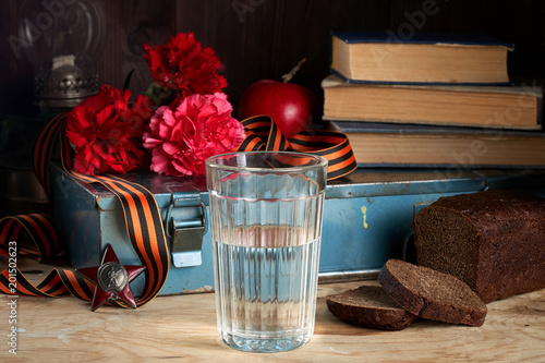 Concept still life of May 9 russian holiday Victory Day. Glass of vodka, rye bread, red carnations, St. George's ribbon