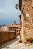 View of an old medieval street Cortona with old bell tower, an old town in Tuscany