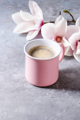 Pink mug of black espresso coffee with spring flowers magnolia branches over grey texture background. Top view, space.