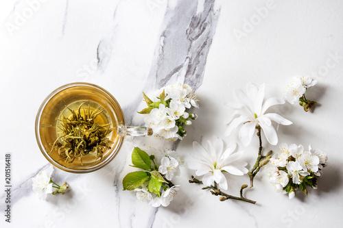Szklana filiżanka gorąca zielona herbata z wiosna kwiatów magnolii i bielu kwitnącymi gałąź nad bielem wykładamy marmurem tekstury tło. Widok z góry, kopia przestrzeń.