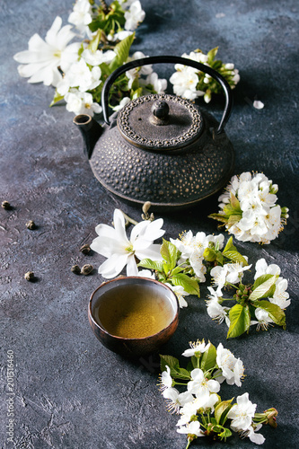 Fototapeta Traditional ceramic cup of hot green tea with black iron teapot, spring flowers white magnolia and cherry blooming branches over dark blue texture background. Copy space.