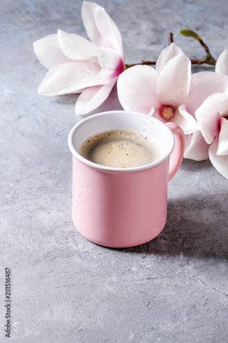 Foto Murales Pink mug of black espresso coffee with spring flowers magnolia branches over grey texture background. Top view, space.