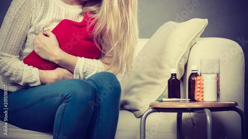 Foto Murales Woman feeling stomach cramps sitting on cofa