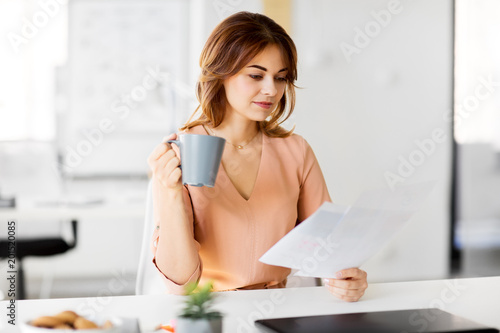 Wall mural business and people concept - businesswoman with papers at working office and drinking coffee