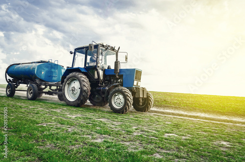 Foto Murales tractor of blue color with a barrel trailer rides along the spring field along the road