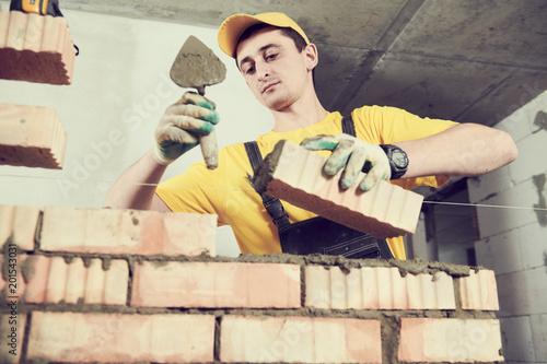 Foto Murales bricklayer builder worker laying bricks wall