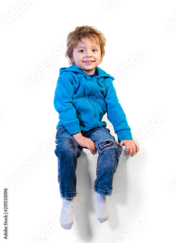 A little child of three years sits and laughs. Isolated on a white background