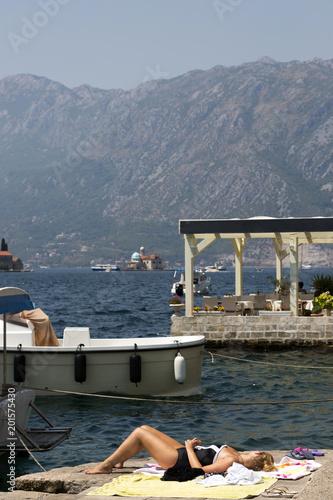 Foto Murales Perast, Montenegro - August 04, 2017: Girl sunbathing on the sun on the waterfront