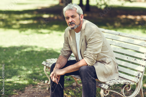 Foto Murales Pensive mature man sitting on bench in an urban park.