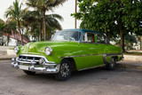 Old green American car parked in Cienfuegos