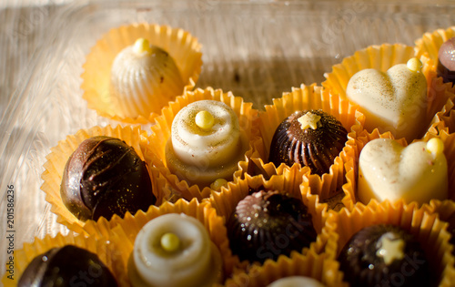 small brown and white chocolate handmade cakes in yellow paper baskets close up