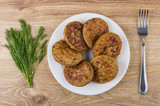 Fried cutlets in white plate, bunch of dill and fork - 201621844