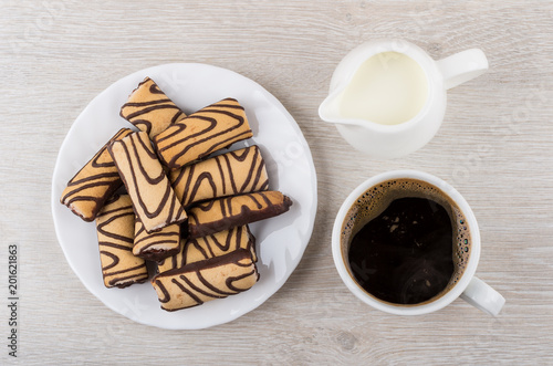 Wall mural White plate with striped cookies, jug of milk and coffee