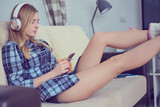 Side view of a girl in casual clothes listening music and selecting songs on a smart phone lying in a couch at home. - 201628494