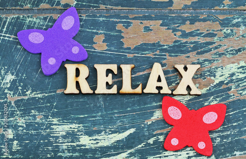 Word relax written on rustic wooden surface and two colorful butterflies