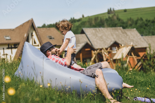 Father and son resting on an air sofa in the mountains. lamzac. Travel.